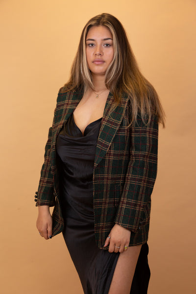 The Harrison Tartan Blazer is dark green in colour with a brown and red tartan design, dark green buttons down the front and on the sleeves and large front pockets.