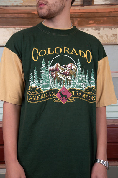 green tee with contrasting beige sleeves and neckline detailing, along with graphic of colorado nature and spell-out above