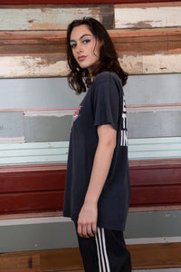 model is wearing a university style graphic on the front showing a big cat clawing through the shirt. The tee is faded black model is wearing a university style graphic on the front showing a big cat clawing through the shirt. The tee is faded black