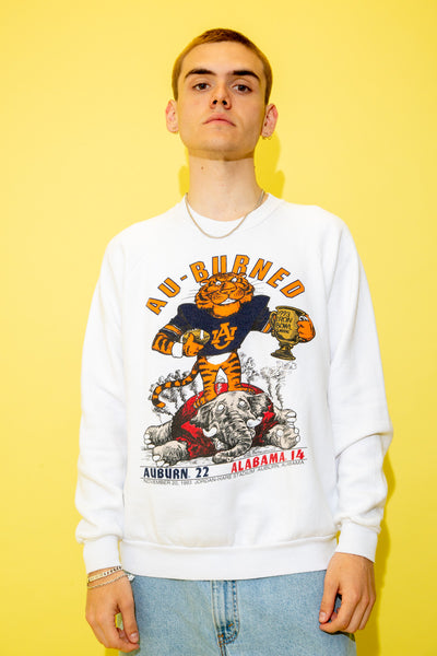 The model is wearing a white sweater that features a tiger on the front and scores on the back