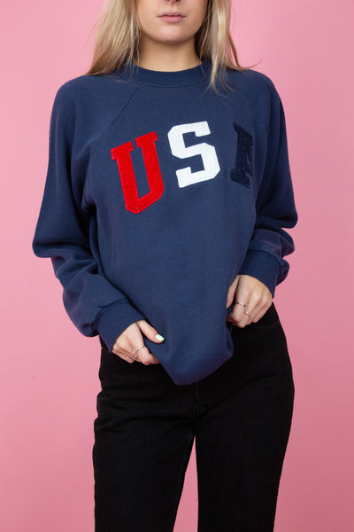 Female model wearing a vintage navy USA sweater