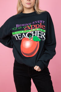 female model wearing a vintage black sweater with large apple front graphic