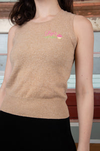 model is wearing a light brown knitted cashmere vest that features a Gigi's cupcakes logo on the left side with. the name in script and the cup cake right next to it.