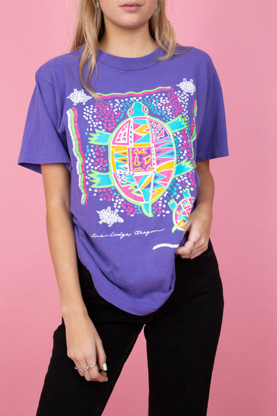 female model wearing a vintage purple tee shirt with colourful turtle graphics on both the front and the back