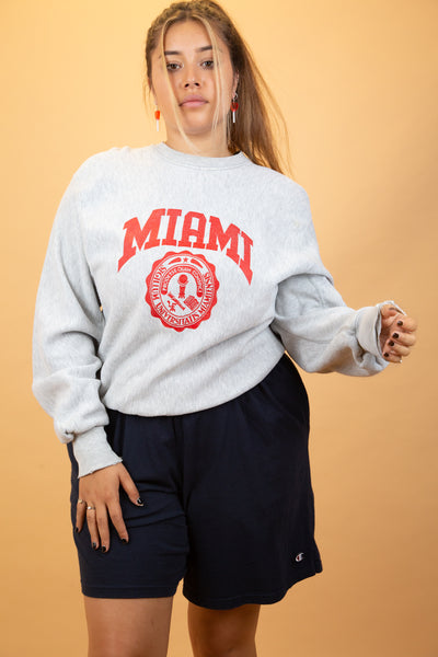 This reverse weave sweater is grey in colour with a red Miami spell-out on the front and the University of Miami emblem below. Distressing along the neckline and sleeves.