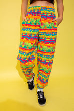 Load image into Gallery viewer, The model is wearing relaxed pants with a rainbow mickey mouse print all over