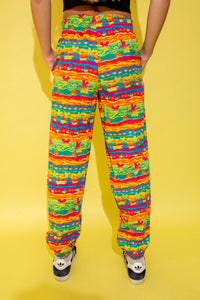 The model is wearing relaxed pants with a rainbow mickey mouse print all over