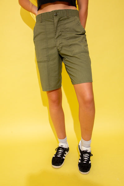 The model is wearing knee length khaki green shorts