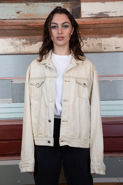 the model is wearing a cream denim jacket, the jacket has contrast stitching.This denim jacket is made by Calvin Klein