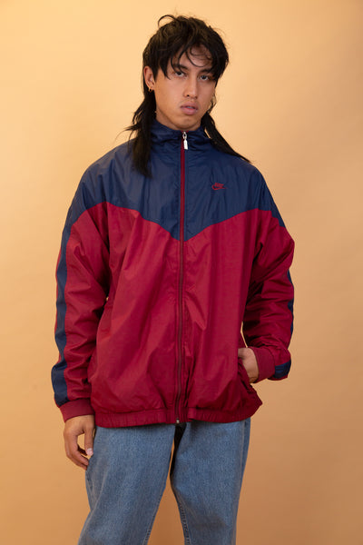 This Nike windbreaker is navy blue and maroon with an anorak outer shell and soft inner shell. With Nike branding on the left chest and on the zip.