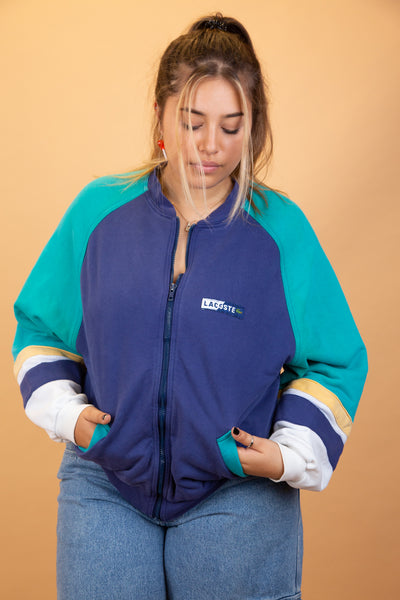 This navy zip-up has light blue sleeves with yellow and white horizontal stripes across the bottom of the sleeves, blue lined pockets and branding on the left chest.