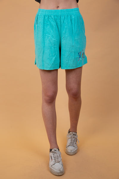teal/turquoise shorts with cute little dancing people on the left leg
