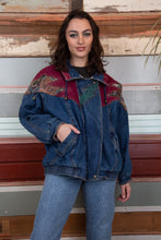 Load image into Gallery viewer, the model is wearing a patch work denim jacket that has patterns on the shoulder, the jacket is thick looking and fits oversized on the model