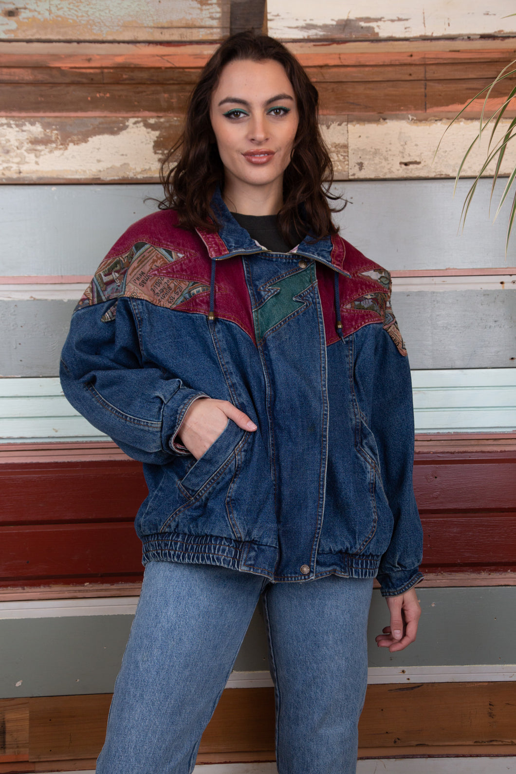 the model is wearing a patch work denim jacket that has patterns on the shoulder, the jacket is thick looking and fits oversized on the model