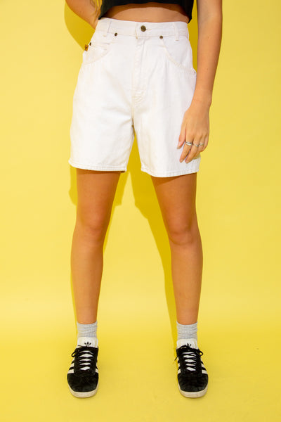 The model is wearing mid thigh length white denim shorts