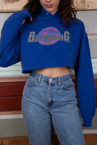 blue sweater with a hood and it has been cropped. Bodyboarding graphic on the front. vintage clothing at magichollow