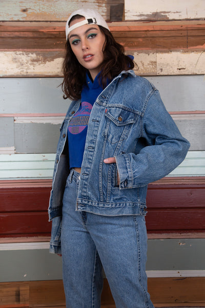 model is wearing a mid wash denim jacket, with four pockets including two on either side of the chest and two on the bottom