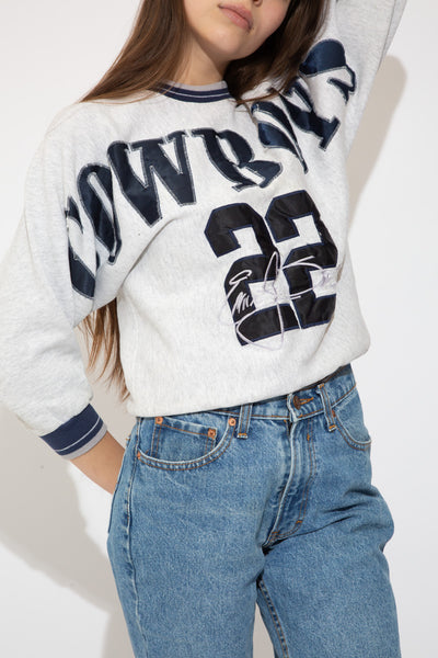 grey crewneck with large dallas cowboys spell-out across chest and arms