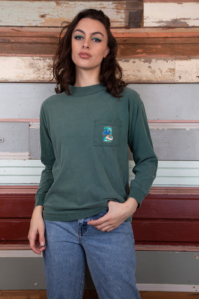 model is wearing a green L/S top made by Harley Davidson, the tee features a small logo on the left side and a massive back print featuring the ever classic Harley bike