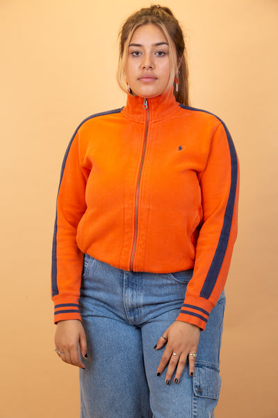 Bright orange zip-up with thick material, navy striped detailing on the arms and collar and branding on the left chest and zip.