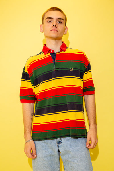 This polo style tee is in a ribbed material and horizontally striped in red, blue, yellow and green. With shell-like buttons, a red collar and the Tommy Hilfiger lion emblem on the left chest