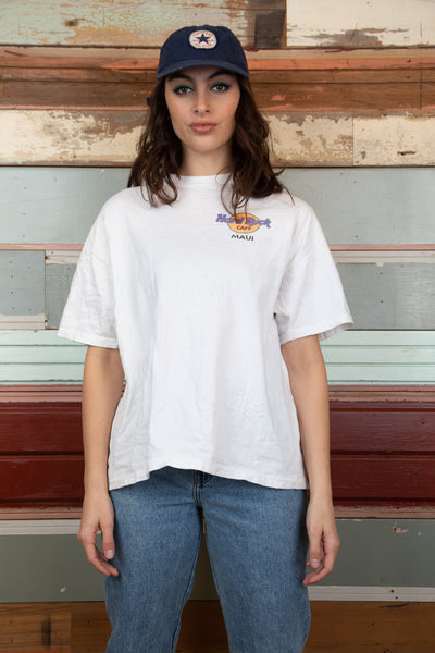 model is wearing a white tee that features a small print on the left side of the Hard Rock logo and a big back print of five surf boards with the logo again over the top of the surf boards.