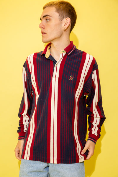 In a polo design with a ribbed feel, this sweater is vertically striped in red, blue and white. Finished off with the Tommy Hilfiger lion emblem on the left chest.