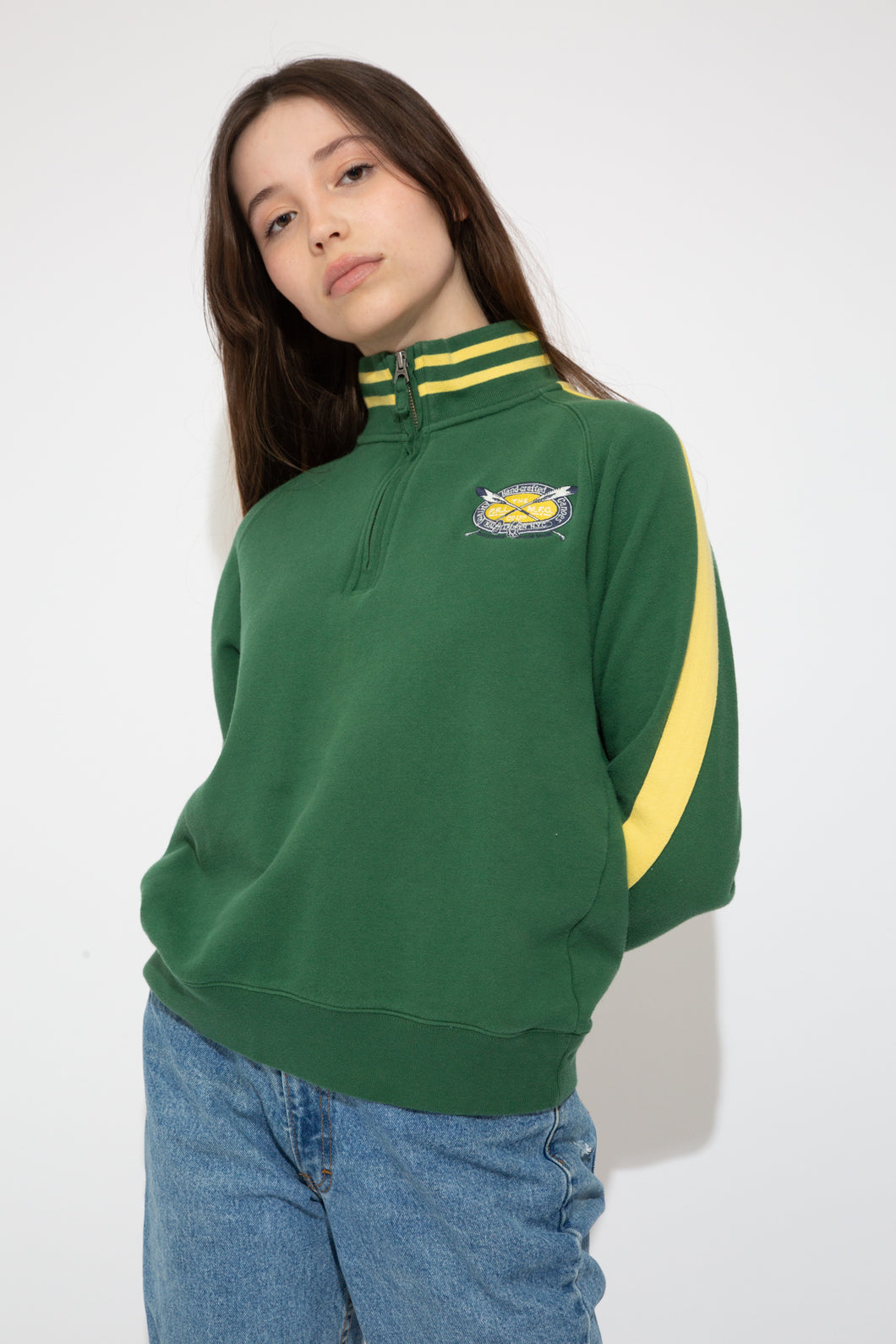 green quarterzip with oval embroidered detailing on left chest and contrasting yellow stripes on collar and down sleeves