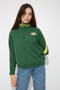 green quarterzip with oval embroidered detailing on left chest and contrasting yellow stripes on collar and down sleves