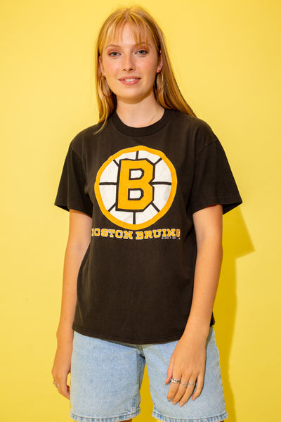 the model is wearing a faded black tee with a boston bruins logo on the front
