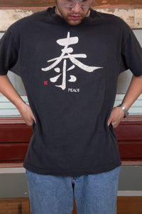 faded black tee with peace symbol graphic and text on front
