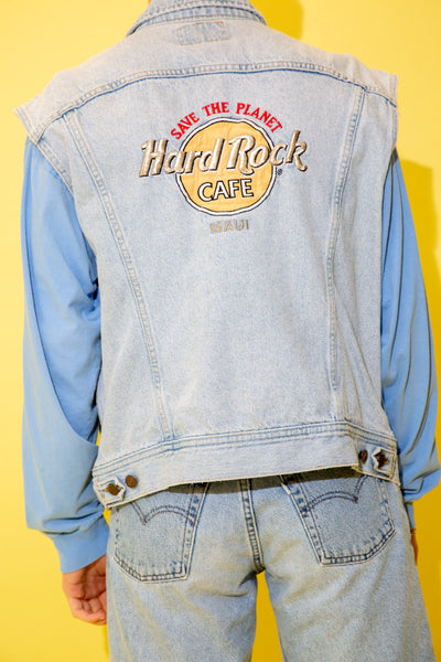 Light wash blue with light brown stitching, this denim vest has four pockets and Lee branding on the buttons and front left pocket. On the back, a large embroidered appliqué of Hard Rock Cafe Maui with a red 'save the planet' spell-out.