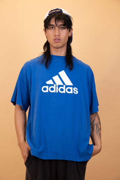 The model is wearing a Adidas shirt that features a massive logo on the front, the top fits oversized. on the model.