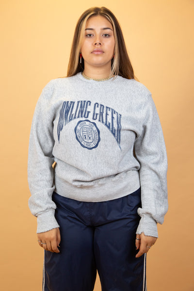 This grey, reverse-weave sweater has a large navy spell-out of 'Bowling Green' across the front with the university logo below. The distressed, stretched-out neckline adds to the baggy, vintage look sweater.