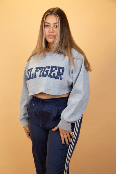 This thick material sweater is grey in colour with a navy appliqué spell-out of 'Hilfiger' across the front. Stretched out neckline adds to the baggy fit.