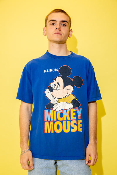 The model is wearing a blue tee that features a massive mickey bigface print on the front