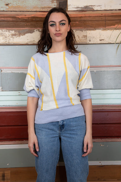 model is wearing a knitted sweater that has a pastel coloured yellow,orange and purple front and then a pastel purple back. This sweater has purple cuffs