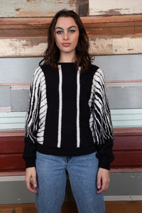 model is wearing a black and white stripped knitted sweater that has a boxy look to it.