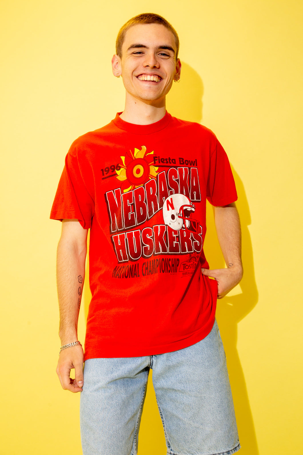 Bright red single-stitch tee with a large Nebraska Huskers print across the front, this tee reps the Fiesta Bowl with a helmet print, a sun print and dated 1996.