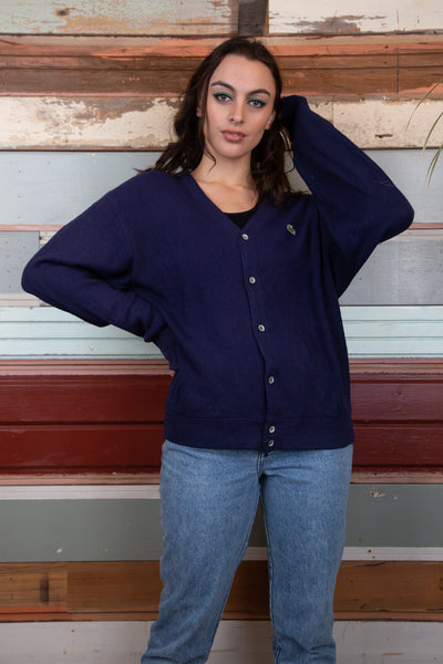 model is wearing a navy Lacoste knitted cardigan. The cardigan is oversized and features a green crocodile on the left side of the chest