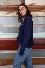 Load image into Gallery viewer, model is wearing a navy Lacoste knitted cardigan. The cardigan is oversized and features a green crocodile on the left side of the chest