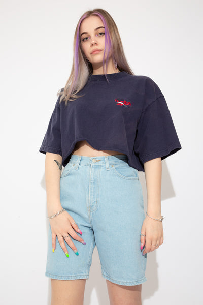 Navy blue cropped tee with a red and white Reebok logo embroidered on the left chest and thick material.