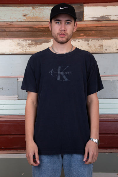 faded and distressed black tee with CK logo on chest