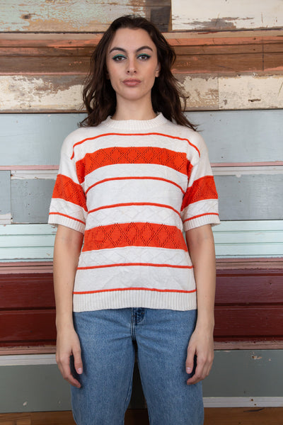 model is wearing a striped orange and white short sleeve knitted top, ribbed neck and sleeves.
