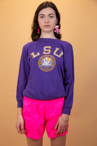 "purple sweater with yellow and white ""LSU"" graphic on the front"
