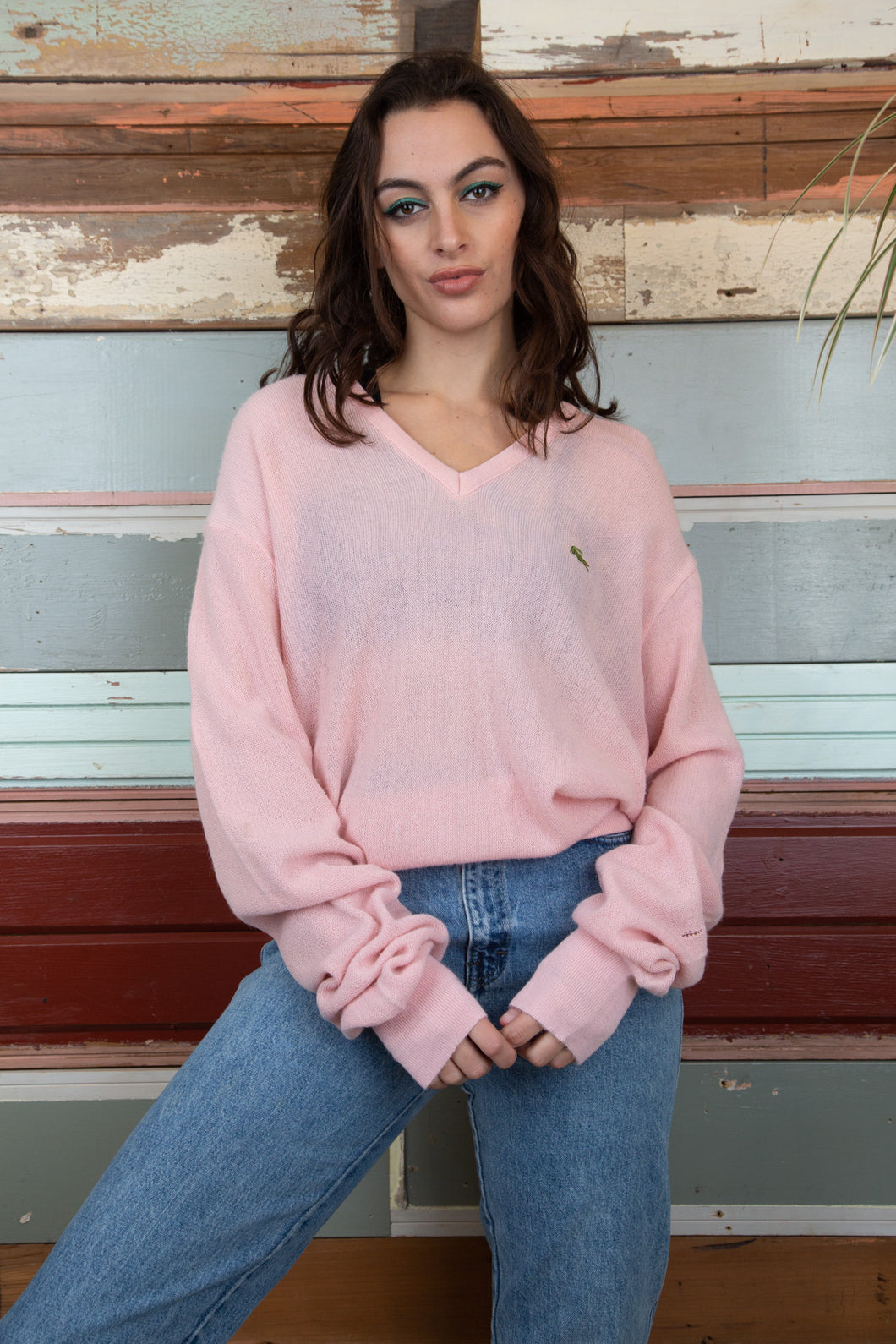 the model is wearing a pink knitted sweater is made by Lacoste, the knit fits oversized on the model.
