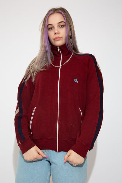 This Lacoste Zip-Up is maroon red in colour with navy blue and grey stripes down the arms and a navy and grey Lacoste logo on the left chest. Finished of with a white closing zip and white zip-up pockets