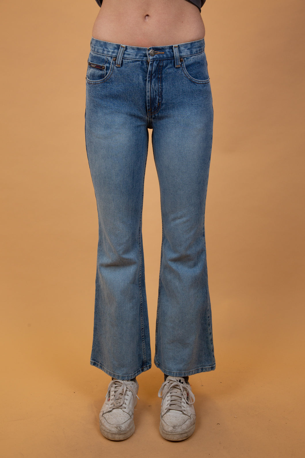 mid-wash low-rise blue jeans that flare out from the knee down.