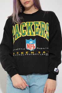 Black sweater with a large green and yellow Packers' print and 'Green Bay' printed below with the NFL logo. Dated 1994 with the Logo Athletic branding on the left sleeve.