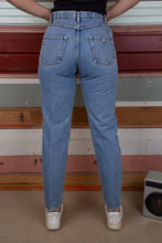 Load image into Gallery viewer, model is wearing mid wash blue denim jeans made by guess these jeans feature the iconic tringale logo on t he back and are slightly high waisted